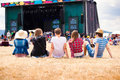 Teenagers, summer music festival, sitting in front of stage Royalty Free Stock Photo