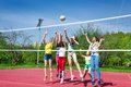Teenagers team actively playing volleyball game on the court during sunny summer day outside Royalty Free Stock Photo