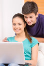Teenagers two cheerful looking at computer monitor and smiling Royalty Free Stock Photo