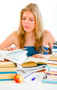 Teengirl sitting at table and searching in books Stock Photography
