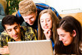 Teens crowd around computer a group of viewing a screen together high saturation Royalty Free Stock Images