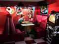 Teens flirt interior of a fifties cafe at a table close to a jukebox couple of is flirting Stock Image