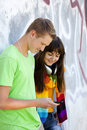 Teens with headphones near graffiti wall. Stock Photos