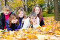 Teens lying on autumnal leaves Royalty Free Stock Photos