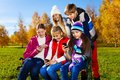 Teens occupied with phones group of school age teen kids looking at their mobile sitting on the bench in autumn park on sunny day Stock Images