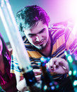 Teens at party doing drugs close up photo of with colorful lights and bong in foreground Stock Photo