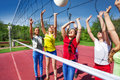 Teens playing actively near the volleyball net on court during sunny summer day outside Stock Photo