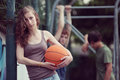 Teens teen girl with basketball her friends on the background Royalty Free Stock Photography