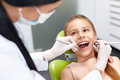 Teeth checkup at dentist's office. Dentist examining girls teeth Royalty Free Stock Photo