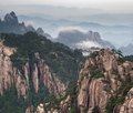 Tele image of huangshan mountain and chinese style house at cloudy weather sunset aerial view at yellow china asia Stock Photos