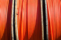 Telecom cable tubing close up photo image of three drum rolls of orange colored it for internet telephone communications Stock Photo