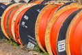 Telecom cable tubing drums close up photo image of it network rolls of orange colored it for internet telephone communications Stock Photography