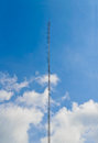 Telecom tower for radio mobile against blue and cloudy sky Royalty Free Stock Image