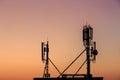 Telecom transmitter station sunset with base Stock Image