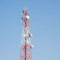 Telecommunication mast with microwave link antennas over a blue sky Stock Photo