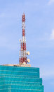 Telecommunication tower with antennas on the top of glass building Stock Photos