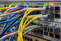 Telecommunications rack with switches and colored UTP and fiber Royalty Free Stock Photo