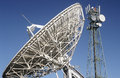 Telecommunications satellite dish and communications towers Royalty Free Stock Photo