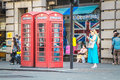 Telephone booths london united kingdom july people are on the sidewalk beside two red phone in Stock Photo
