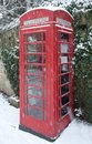 Telephone box in snow english red winter against an ivy clad cotswold stone wall Royalty Free Stock Photography