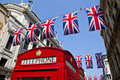 Telephone Box and Union Flags in London Royalty Free Stock Photo