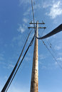 Telephone pole with wires coming to the ground and cables from a come Royalty Free Stock Images