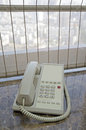 Telephone on windowsill with curtain and city view Royalty Free Stock Image