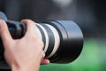 Telephoto lens shooting camera with pro grade in photographer s hands Royalty Free Stock Photography