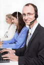 Telesales or helpdesk team helpful man with headset smiling at men camera workers callcenter male and female Stock Photo
