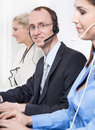 Telesales or helpdesk team helpful man with headset smiling at men camera workers callcenter male and female Royalty Free Stock Images