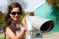 Telescope a young woman enjoying a view through a Royalty Free Stock Photo