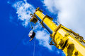 Telescopic arm of a mobile crane yellow against deep blue sky and white clouds Royalty Free Stock Photos