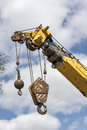 Telescoping mobile crane with hooks a lifting is suspended high above the ground waiting to pick up its cargo room in the sky for Stock Photo