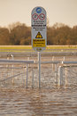 Temporary surface a sign at a racecourse standing in floodwater suggesting this is a Royalty Free Stock Image