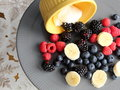 Tempting fresh berries and dip on gray plate Royalty Free Stock Photos