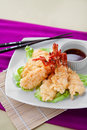 Tempura crispy japanese on a bed of lettuce served with sauce arranged on a tabletop against a bamboo mat and a bright Royalty Free Stock Photo