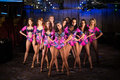 Ten beautiful showgirls in purple costumes posing on stage Stock Image