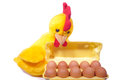 Ten chicken eggs in yellow box with toy rooster (white backgroun Royalty Free Stock Photo