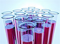 Ten test tubes with pink fluid and shallow DOF Royalty Free Stock Photo