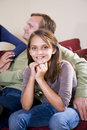 Ten year old girl sitting on sofa next to father Royalty Free Stock Photos