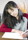 Ten year old girl writing or drawing on paper Royalty Free Stock Photography
