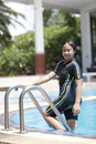 Ten years old girl playing in swimming pool wearing suit Royalty Free Stock Photography