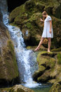 Tender beauty beautiful young woman with flowing hair in white sundress stands above the waterfall on mossy rock Stock Images