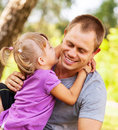Tender family scene in park little daughter try to kiss her father Stock Photography