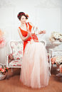 Tender girl in the room with flowers a red dress holding a tutu and ballet pointe shoes around there are Royalty Free Stock Images