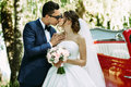 Tender kiss of the two in their wedding day Royalty Free Stock Photo