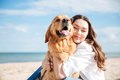 Tender smiling young woman hugging her dog on the beach Royalty Free Stock Photo