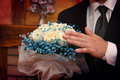 Tender touching groom examining wedding bouquet photo taken in Stock Image