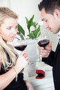 Tender young couple celebrating together holding glasses of red wine with a red ring box or jewellery gift box standing on the Stock Photos