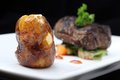 Tenderloin steak portion with potato on black background focus on potato Royalty Free Stock Image